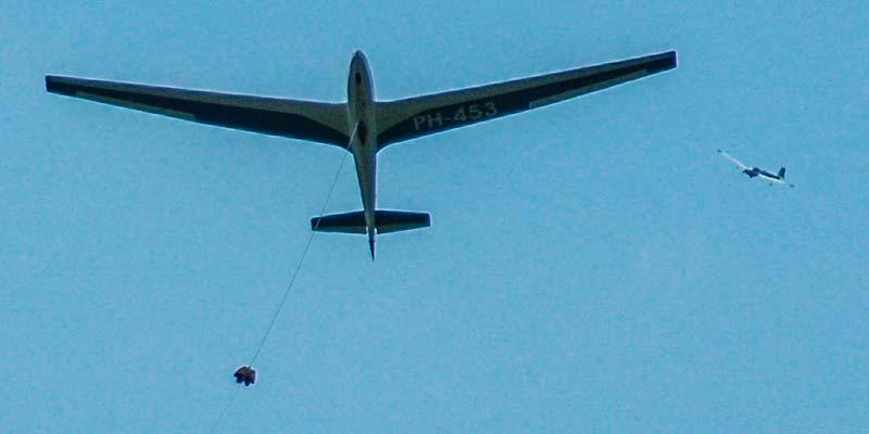 Topdrukte bij Vliegveld Hilversum. Een zweefvliegtuig wordt met een lier omhoog getrokken. In de verte komt alweer een ander toestel aan om te landen